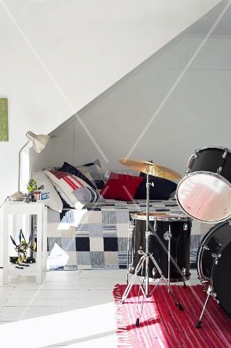 Bett Mit Patchwork Tagesdecke Unter Dachschräge U0026 Schlagzeug In Jugendzimmer