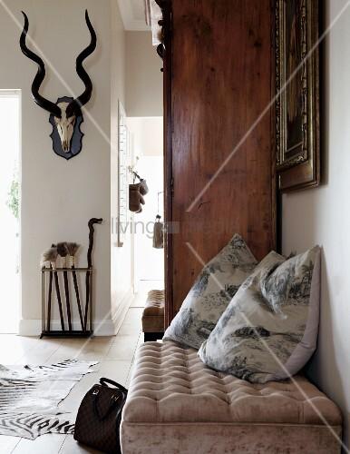 kissen auf polsterhocker neben antikem schrank im hintergund tiertroph e an wand bild kaufen. Black Bedroom Furniture Sets. Home Design Ideas