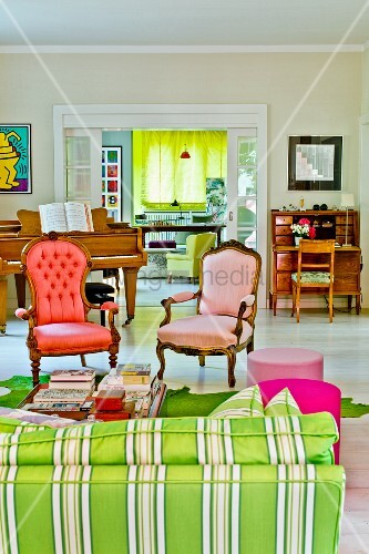 Complementary shades of red and green - Rococo armchairs with modern upholstery, striped sofa and curtain in background