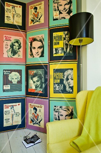 Collection of fifties portraits of women on wall behind retro standard lamp and yellow armchair