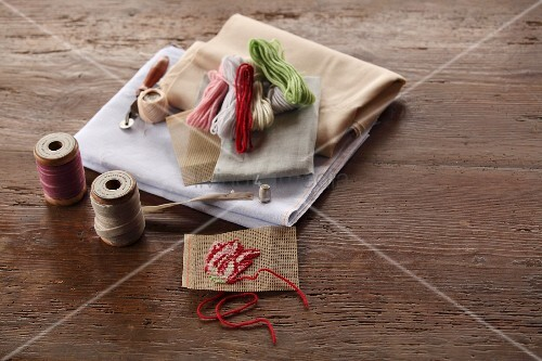 Reels of yarn, hand-embroidered sample and various fabrics on rustic wooden surface