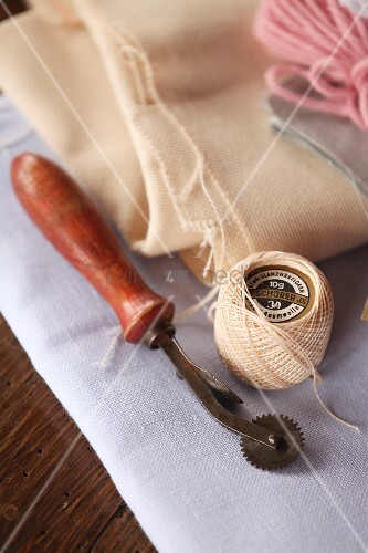 Reel of yarn and cutting utensil on folded fabric