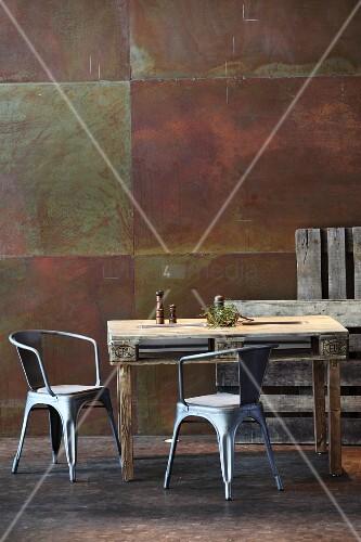 Rustikaler Esstisch aus Palette und Metallstühle vor Cortenstahl Wand