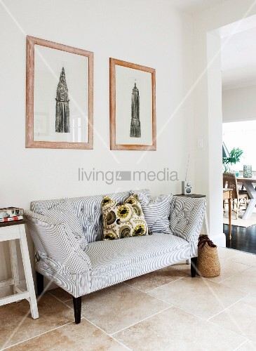 Framed drawings above two-seater sofa with pattern of narrow stripes in tiled hallway