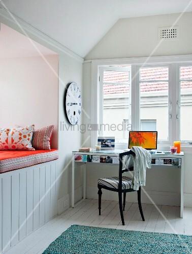 Freundliches Schlafzimmer mit weiss lackiertem Dielenboden und Holzverkleidung am Alkoven; daneben Antikstuhl an modernem Computertisch