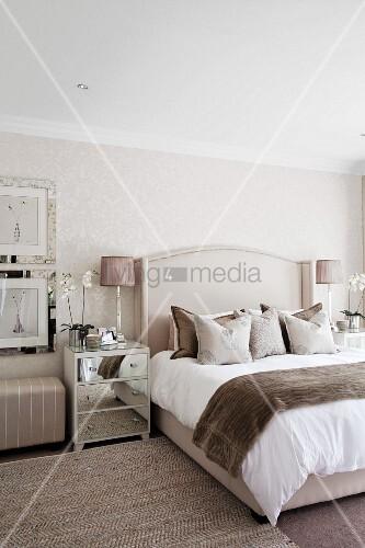 In Beigetönen gestaltetes Schlafzimmer mit Dekokissen und ...