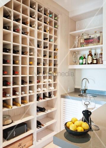 Moderne Küche mit Weinlager in Einbauregal, vorne Schale mit Zitronen auf Theke