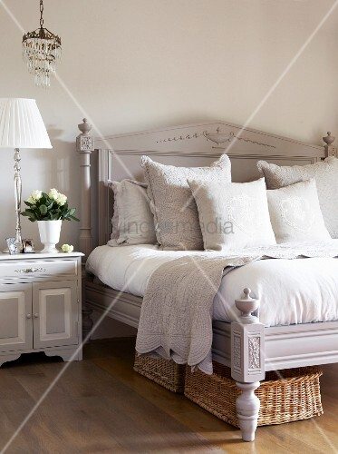 Hellgraues antikes Bett mit Kopfteil und Schnitzereien neben Nachtkästchen und Tischleuchte