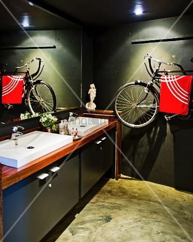 Dark-painted bathroom with modern washstand and bicycle hung on wall used as towel rack