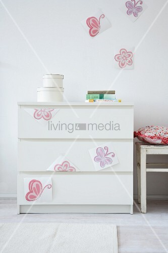 Stickers positioned provisionally on chest of drawers and wall