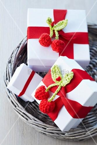 Kleine Geschenkkartons verziert mit rotem Schleifenband und gehäkelten Kirschen