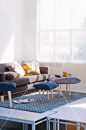 Originelle Hocker mit Sitzkissen und Sofa mit großen Zierkissen in sonnendurchfluteter Raumecke