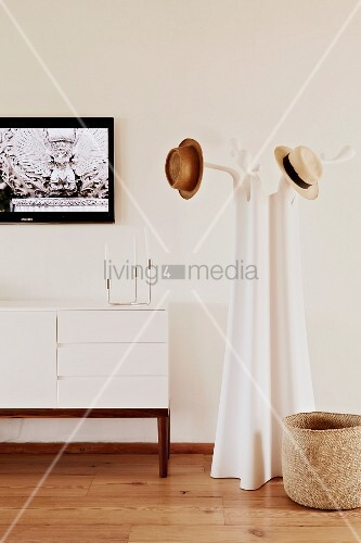 Old-fashioned hats on designer coat rack next to white sideboard with wooden frame below framed picture
