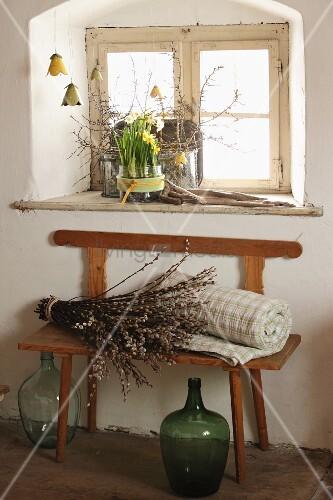 Bunte Blechblüten vor dem Fenster, Narzissen auf der Fensterbank und Weidenkätzchen auf Sitzbank