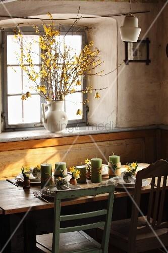 Frühlingshafter Esstisch mit Kerzen und Blumen vor Fenster, Forsythien in Porzellankrug auf Fensterbank