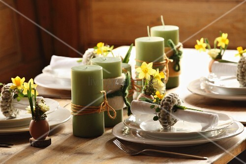 Grüne Kerzen aufgereiht zwischen Gedecken mit österlichem Deko