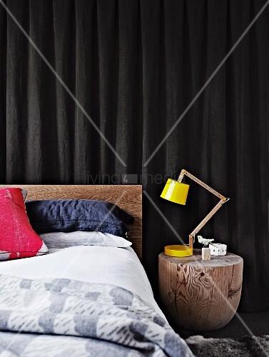 Geschliffener Baumstamm als Nachttisch mit gelber Designer Schreibtischlampe neben Bett