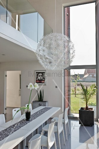 Spherical pendant lamp with white flower details above modern, white dining area with glossy floor below gallery with glass balustrade