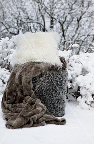 Fur blanket and flokati cushion in snow