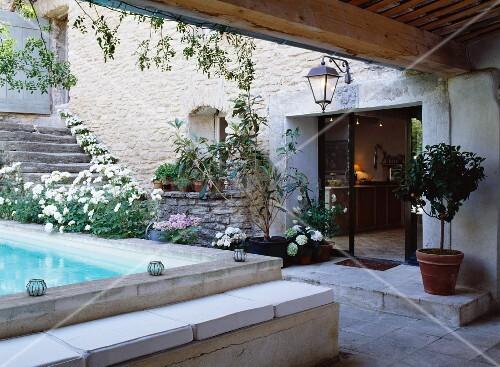 Französisches Landhaus mit Pool im mediterran bepflanzten Innenhof ...