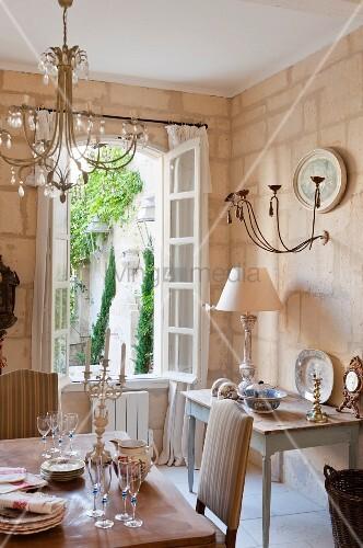 Esszimmer Mit Shabby Chic Flair In Nostalgisch Romantischem Französischen  Landhaus, Blick Durch Geöffnete Sprossenfenster In Begrünten Innenhof