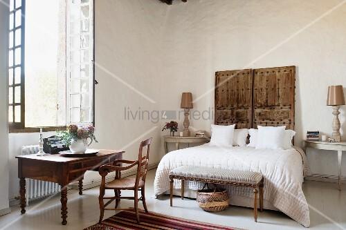 Zwei Alte Türen Als Kopfteil Von Doppelbett Und Antiker Schreibtisch Vor  Sprossenfenster Im Geräumigen Schlafzimmer