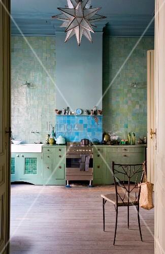 Blick durch geöffnete Tür auf grüne Küchenzeile vor grün gefliester Wand