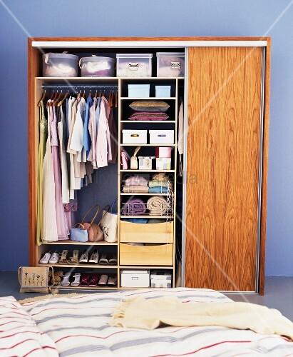 Offener Kleiderschrank vor blauer Wand