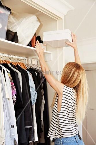 Blonde Frau mit langen Haaren greift eine Schachtel aus dem obersten Kleiderfach eines weißen Kleiderschrankes
