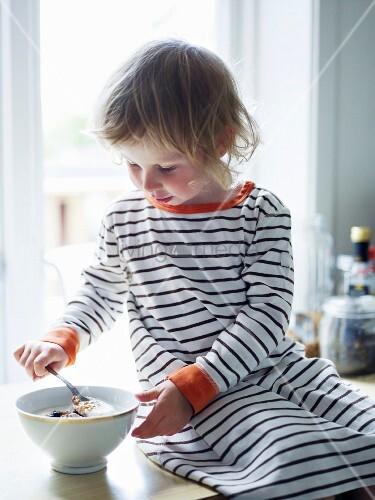 Kleines Mädchen isst Müsli auf einer Küchenarbeitsplatte