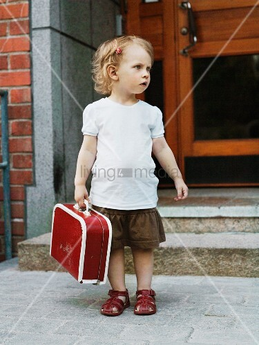 Blonde little girl holding red suitcase waiting outside front door