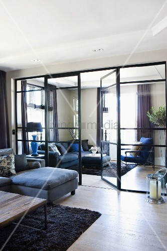 Seating in two large living rooms separated by glass partition wall and glass doors