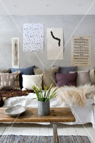 Shabby chic seating area with furs and scatter cushions on sofa; artistic pages pinned on concrete wall and jar of narcissus o vintage bench used as coffee table