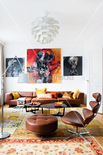 Classic office chair with brown leather cover and footstool in front of lounge area with black coffee table and brown leather sofa below expressive paintings on wall