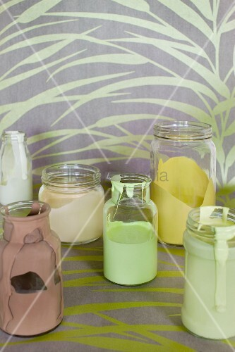Various paints in glass jars on length of yellow patterned wallpaper