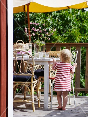 Toddler in summer dress standing next to terrace table