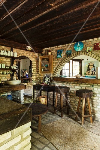 Kitchen in Brazilian cult house with brick walls and dark wooden ceiling; rustic bar stools in front of brick archway and image of the sea goddess of the Candomblé religion