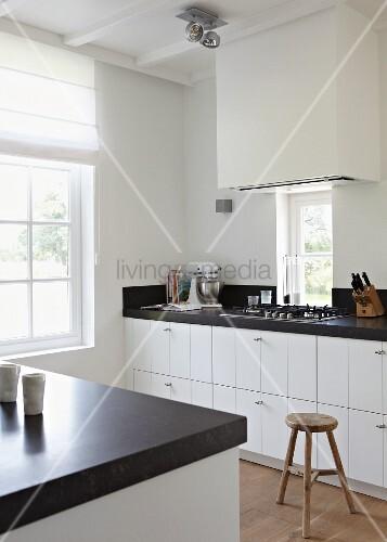 moderne k che in weiss und schwarz und einem vintage hocker bild kaufen living4media. Black Bedroom Furniture Sets. Home Design Ideas