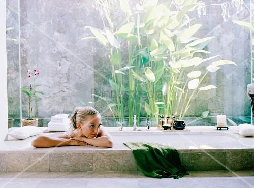 junge frau entspannt in einer im boden eingelassenen badewanne bild kaufen living4media. Black Bedroom Furniture Sets. Home Design Ideas