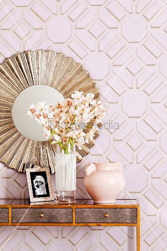 Delicate console table with feminine decor below round, gilt mirror on geometric wallpaper