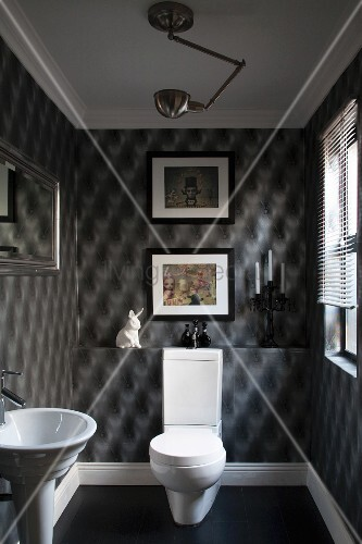 Guest toilet with grey optical art wallpaper and framed pictures; white pedestal toilet with cistern and pedestal washbasin to one side