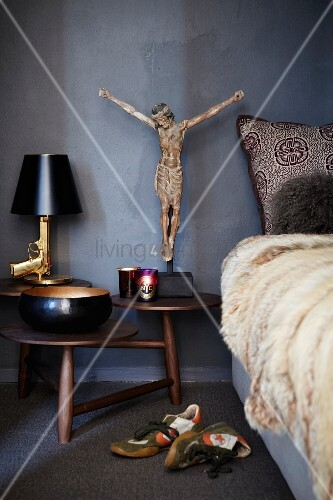Bedside Gun table lamp and Jesus figurine on wooden bedside table with multiple round surfaces next to bed with fur blanket and sports shoes on floor