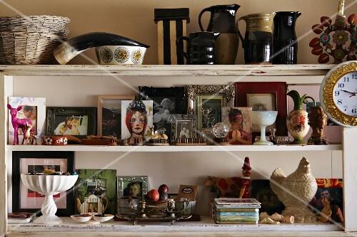 Collection of framed photos, ceramic vases and animal horn on white, shabby chic shelves