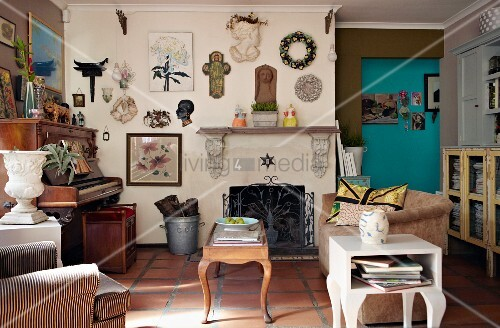 Living room with piano, vintage furniture and wall decorated with collector's items above open fireplace with wrought iron screen