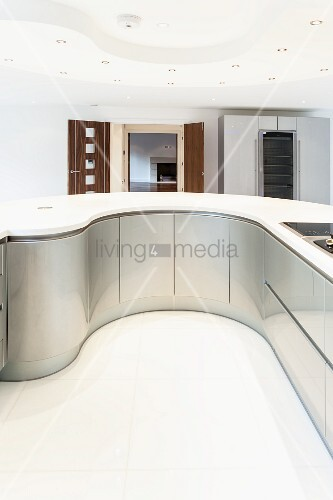 Curved kitchen counter with white worksurface in ultra-modern interior