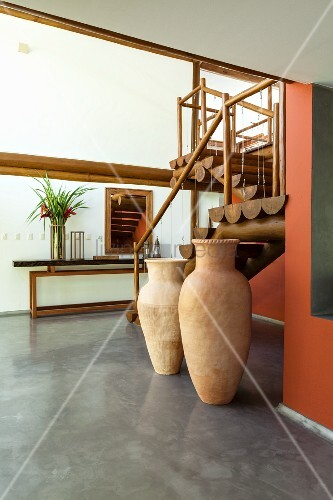 Interior with wooden staircase and floor vases