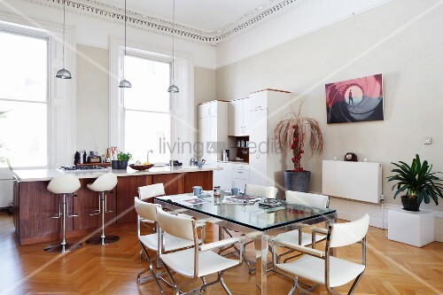 esstisch mit glasplatte und weisse lederst hle vor offener k che mit barhockern an freistehender. Black Bedroom Furniture Sets. Home Design Ideas