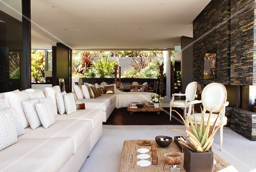 White sofa combination with scatter cushions and rustic low coffee table in front of Neo-Rococo chairs in spacious living room with open fireplace in grey stone wall