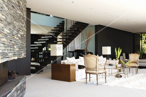 Modern interior with vintage armchairs and modern sofa in front of staircase and black-painted wall in background
