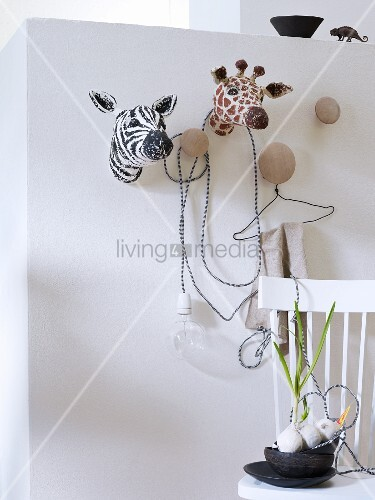 Papier mâché, hunting safari trophies and coat hooks on white wall and black bowls on wooden chair